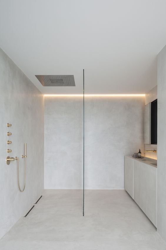 a neutral minimalist bathtoom with sleek walls and a vanity with built in sinks, a shower space and built in lights