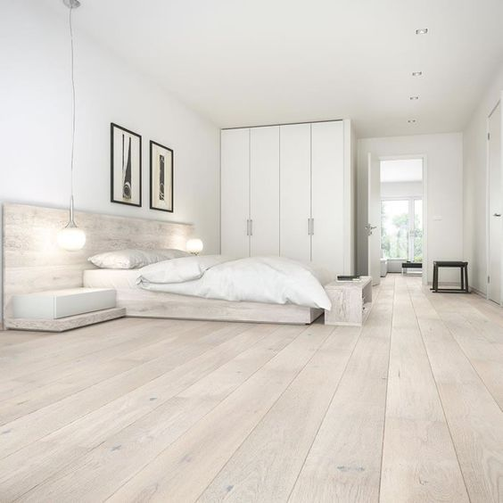 a neutral minimalist bedroom with a large storage unit, a platform bed and built-in nightstands plus pendant lamps