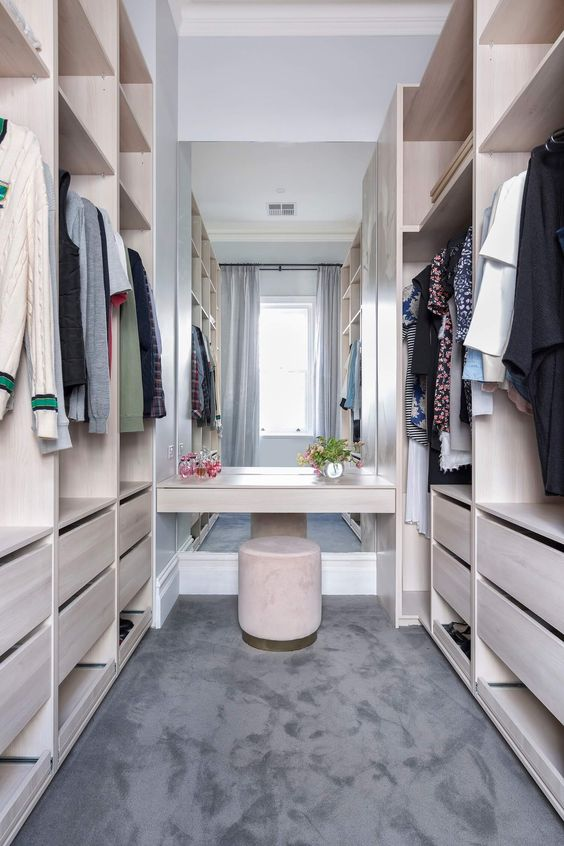 a neutral minimalist closet of neutral plywood, with a large mirror in the center and a velvet ottoman