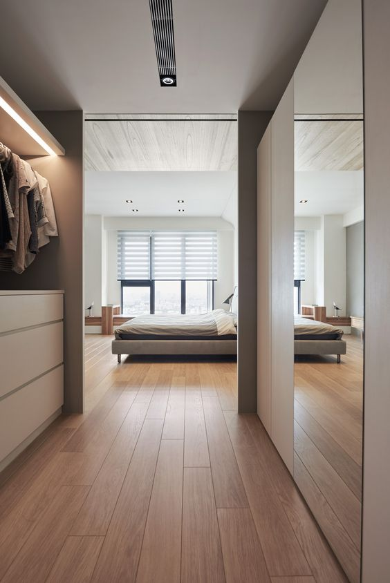 a neutral minimalist closet with a dresser, a holder for hangers, built-in lights and a sleek wardrobe with a mirror