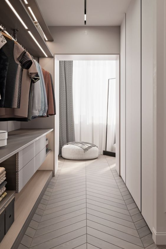 a neutral minimalist closet with a sleek wardrobe, a holder for hangers, built-in lights, drawers, open shelves and boxes