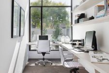 a neutral minimalist home office with a double floating desk, open shelves, artworks and comfortable chairs