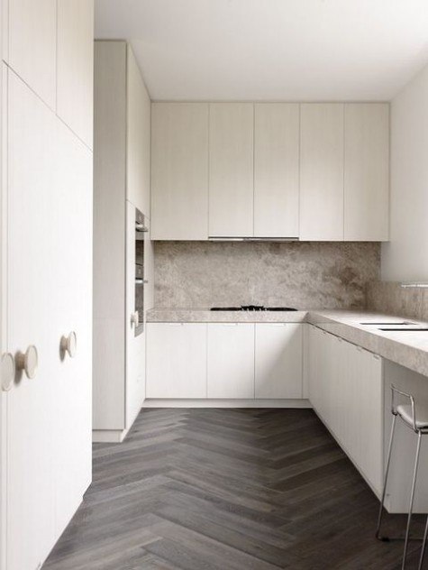 a neutral minimalist kitchen with sleek white cabinets and tan ones, with stone countertops and a backsplash for a texture