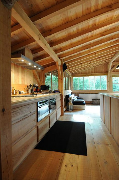 a neutral modern chalet kitchen all clad with wood, with built in appliances and a lounge zone next to it