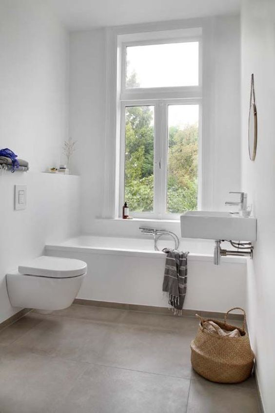 a peaceful minimalist bathroom with white tiles, grey tiles on the floor, a wall-mounted sink and a basket for towels
