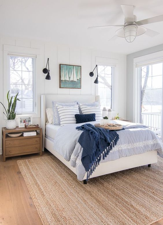 a pretty modern coastal bedroom with beadboard walls, blue bedding, a nautical artwork, wooden furniture and a jute rug