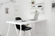 a pure and airy minimalist white home office with a trestle desk, an open shelf, artworks, a lamp and stools