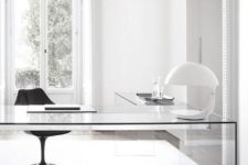 a pure white minimalist home office with a sheer desk, a black chair, a lamp and lots of natural light
