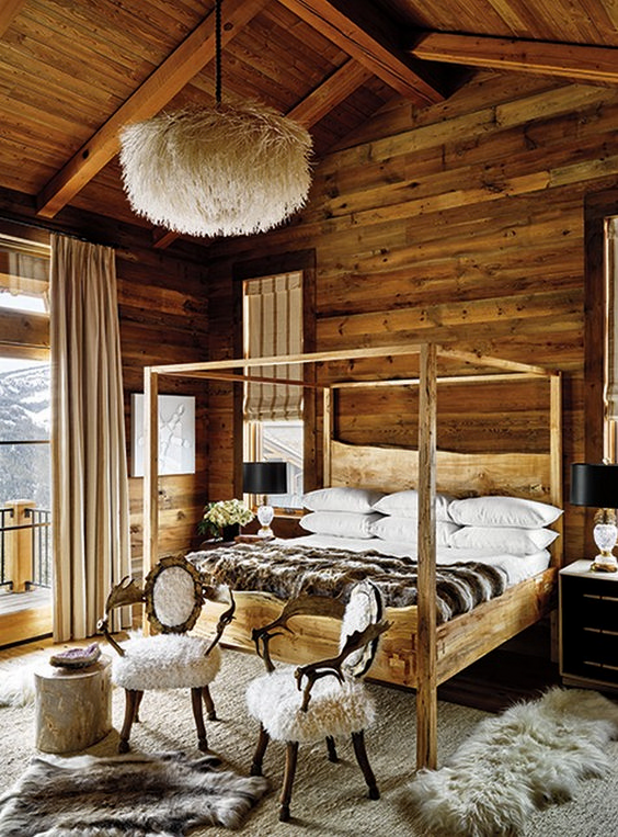 a quirky chalet bedroom fully clad with wood, with a wooden bed, faux fur, a fuax fur lamp and an exit outside