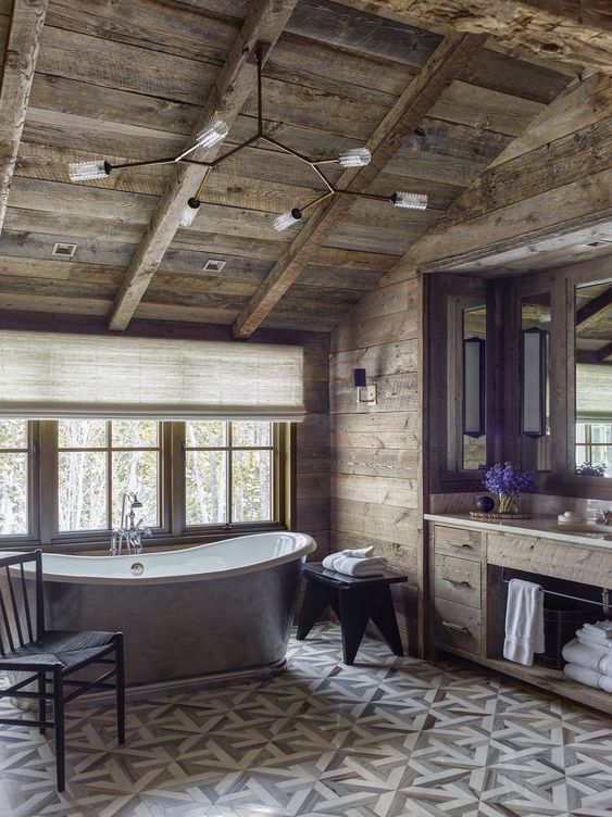 a refined chalet bathroom clad with reclaimed wood, with printed tiles, a metal tub, a built-in vanity, vintage stools and chairs