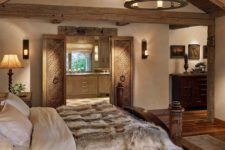 a refined chalet bedorom with carved wooden furniture, a candle chandelier, lots of lamps and faux fur