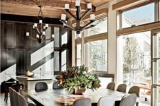 a refined chalet dining room with a large wooden table, mid-century modern chairs, statement chandeliers