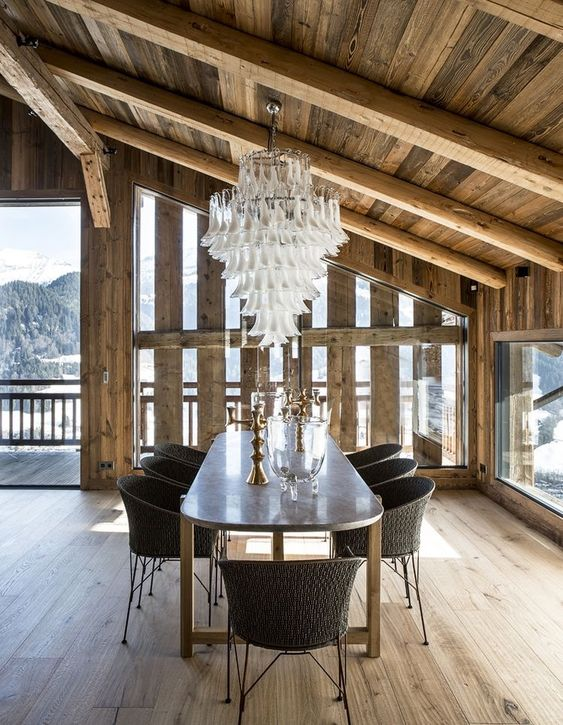 a refined chalet dining room with a metal table, woven chairs, a statement chandeleir and gorgeous views