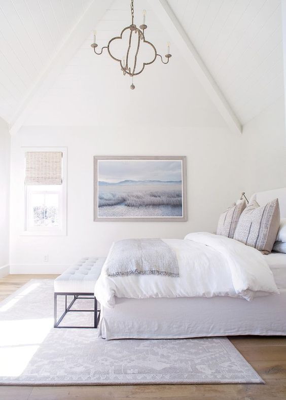 a serene and airy coastal bedroom in neutrals, with a large artwork, woven shades and printed textiles is super cool