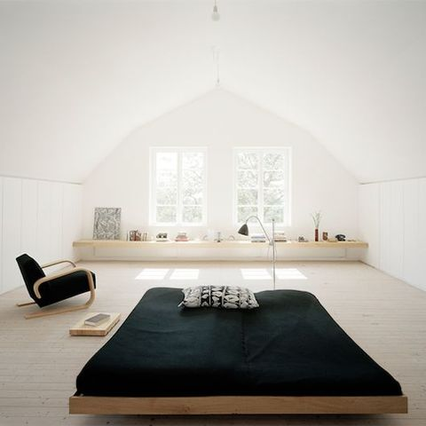 a serene and airy minimalist bedroom with a long shelf along the wall, a simple bed and a matching chair plus black textiles