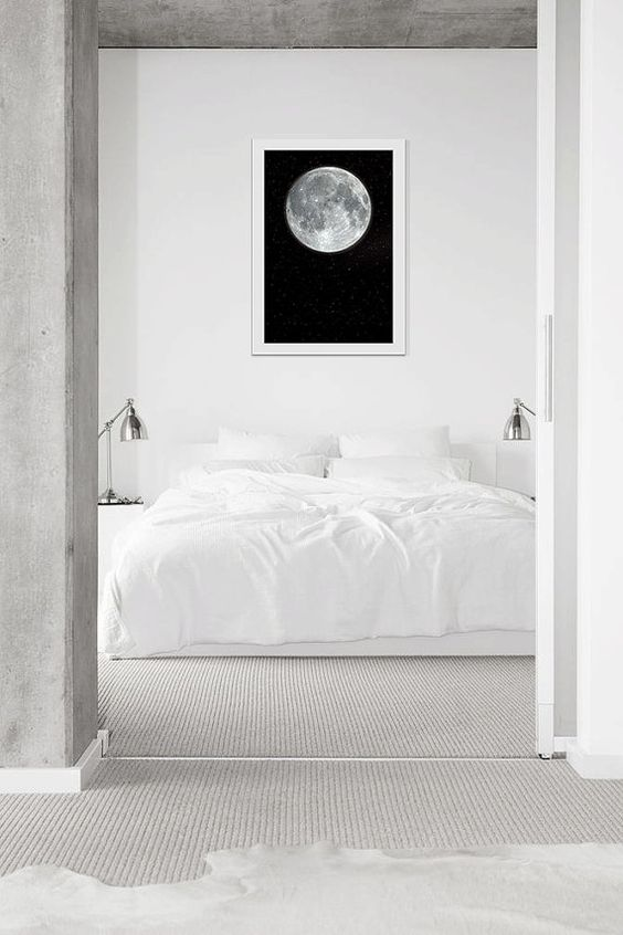 a serene minimal bedroom in white, with a statement artwork, metallic sconces and neutral textiles is very welcoming