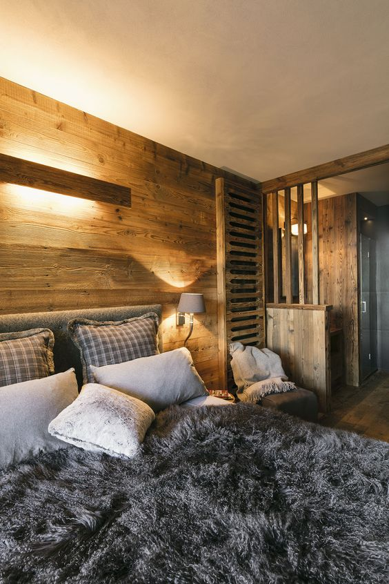 a simple and modern chalet bedroom with light stained wood everywhere, lots of faux fur and cozy textiles
