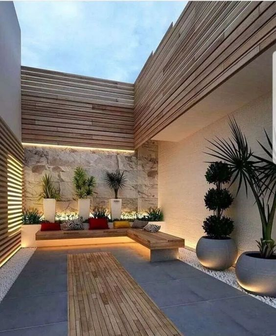 a simple minimalist patio with a corner bench, a deck, colorful pillows and potted plants