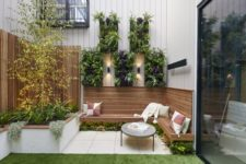 a simple modern backyard with a green lawn, a built-in wooden bench, greenery under the bench and on the walls and pillows