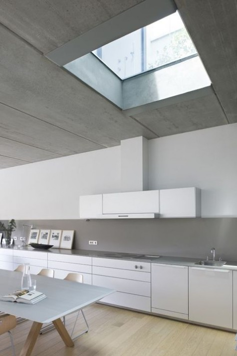 a sleek minimalist white kitchen with lots of cabinets and a concrete backsplash and countertops plus a skylight