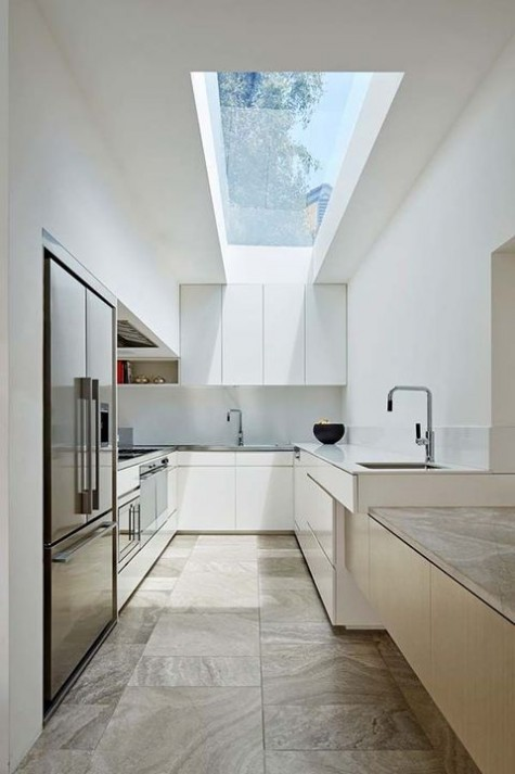 a sleek white minimalist kitchen with elegant cabinets, white countertops, a long skylight and a wooden kitchen island