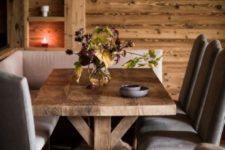 a small and cozy chalet dining nook with a corner sofa, elegant vintage chairs and candles and candle lanterns