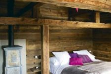 a small chalet bedroom with wooden beams and wooden furniture, a small hearth and colorful bedding