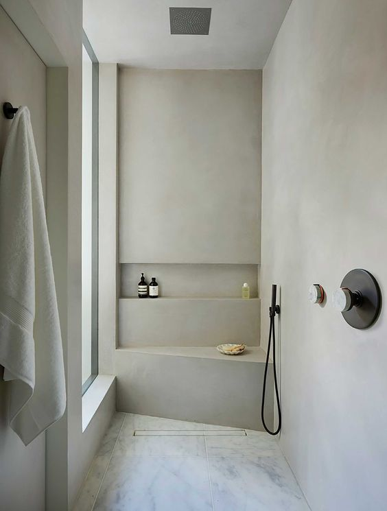 a small minimalist bathroom with marble tiles, concrete walls, black fixtures and a frosted glass window
