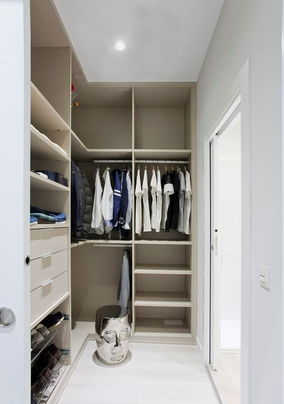 a small minimalist closet with lots of open storage space, dome drawers and holders for hangers, a creative stool and a glass sliding door
