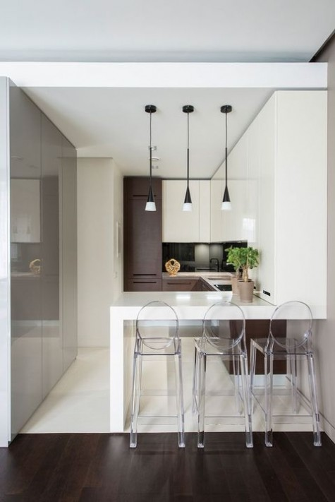 a small minimalist kitchen in white and chocolate brown, wtih a bar, ghost stools and cool pendant lamps