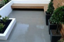 a small minimalist terrace with a long planter along it, black planters with greenery and a wooden bench