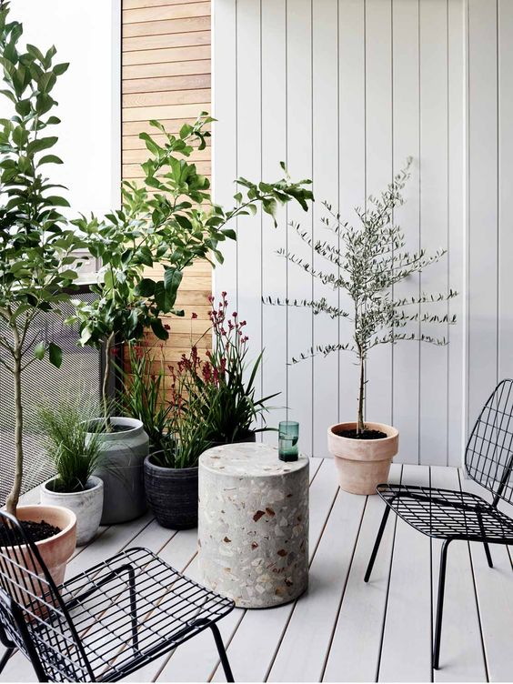 a small minimalist terrace with a white deck, black metal chairs, a terrazzo side table and lots of plants