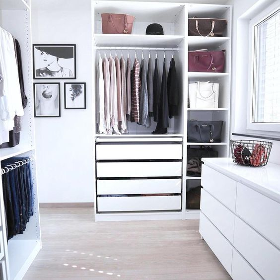 a small minimalist white closet with a dresser, drawers, open shelves and holders and hangers is very neat