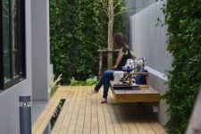 a small modern backyard with a deck and a floating bench plus greenery walls and a tree for relaxing outside
