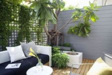 a small modern patio with a storage bench, a metal chair and table and lush greenery here to refresh the space