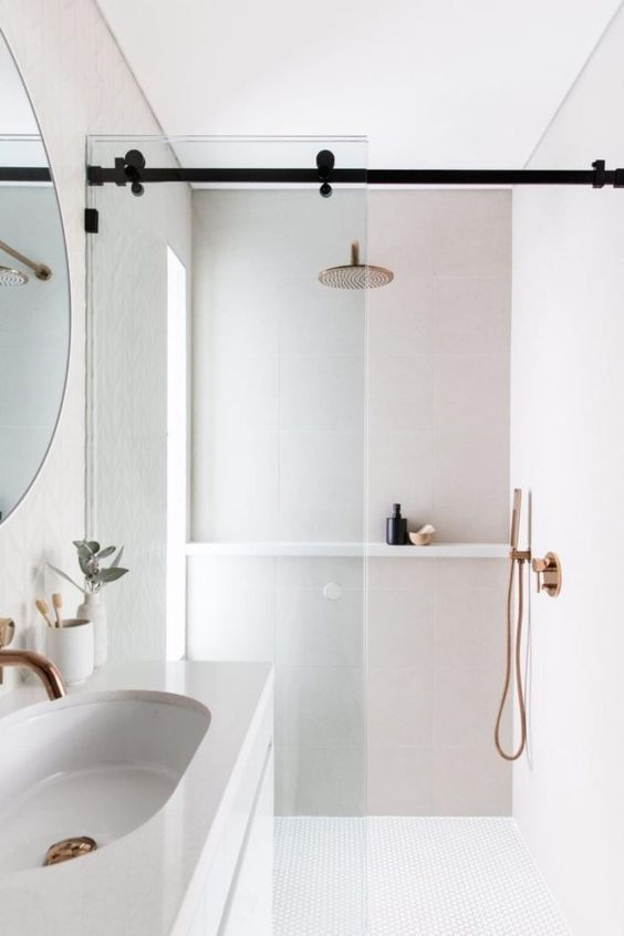 a small neutral bathroom with neutral tiles of various sizes, a floating vanity and a sink, a glass divider and a frosted glass window