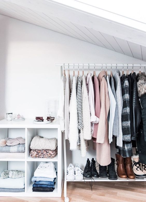 a small white attic closet with an open sideboard, a makeshift closet in the corner and a shelf