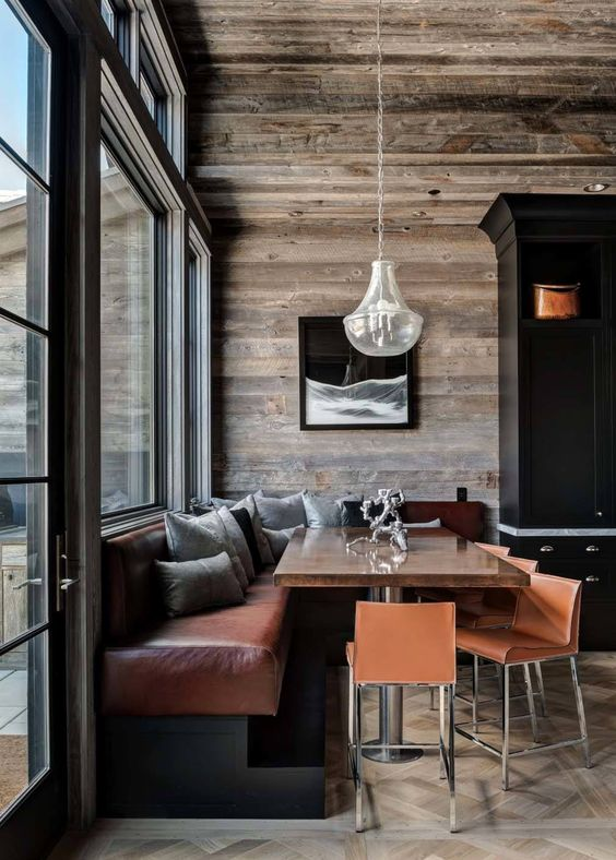 a stylish chalet dining nook with a leather corner bench, leather chairs and a chandelier plus a modern wooden table