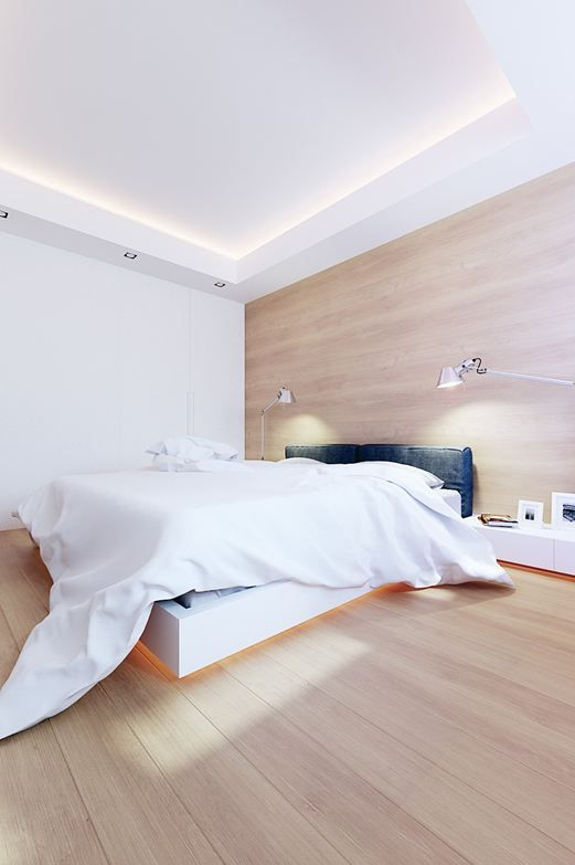 a stylish minimalist bedroom with a white raised bed with lights, an upholstered headboard, some lamps and a large sleek storage unit