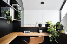 a stylish minimalist home office in black, with open shelves, a floating desk, a leather chair and lots of potted greenery
