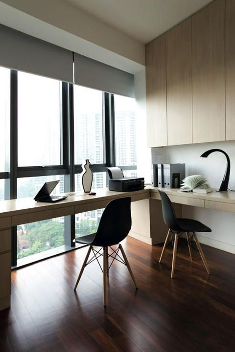 a stylish minimalist home office with a sleek wooden storage unit, a long desk, shades and stylish black chairs