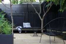a stylish monochromatic backyard with a logn black bench, black chairs and a fire pit plus some trees in here