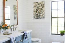a sweet farmhouse bathroom clad with white subway tiles, with a blue vanity, a mirror and gold lamps and sconces
