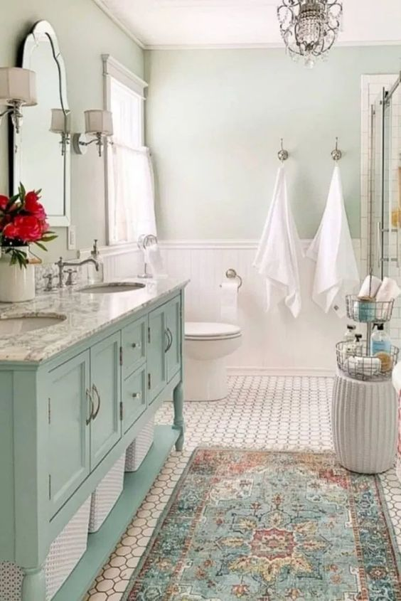 a sweet farmhouse bathroom with light green walls, a blue vanity, a vintage mirror and lamps and a crystal chandelier