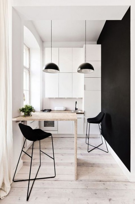 a tiny monochromatic kitchen with sleek white cabinets, a black accent wall, a bar and black stools plus black pendant lamps