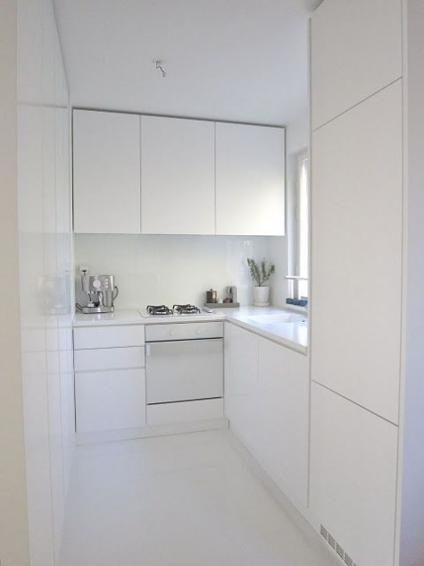 a tiny white minimalist kitchen with sleek cabinets, white countertops and a backsplash looks larger than it is