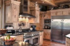 a traditional chalet kitchen all clad with wood, with black stone countertops, a tile backsplash and metal appliances and built-in lights