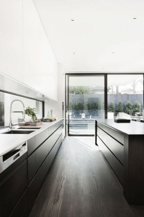 a trendy minimalist two tone kitchen with white uppers and black lowers, a large black kitchen island and white countertops
