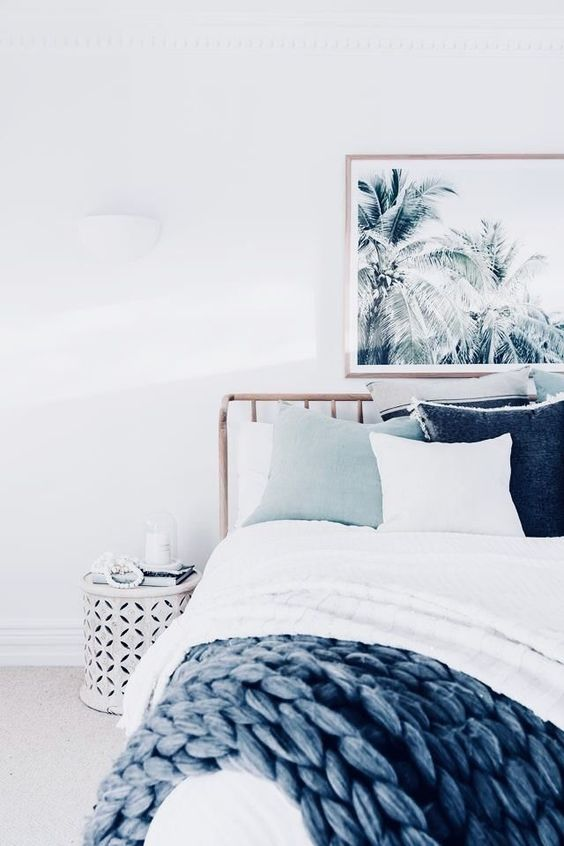 a tropical beach bedroom with a tropical artwork, a wooden bed, coastal-colored textiles, a white perforated nightstand