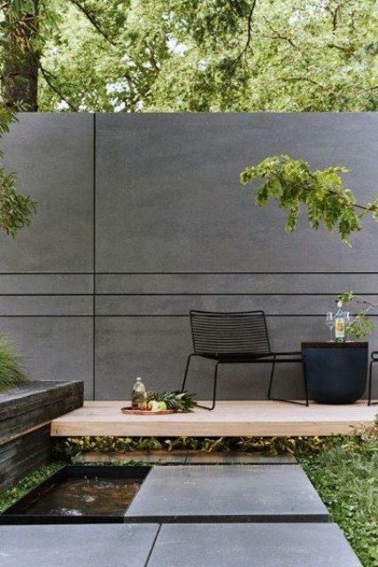 a very laconic backyard with a concrete wall and pavements, a small fountain, a desk with chairs and a side table
